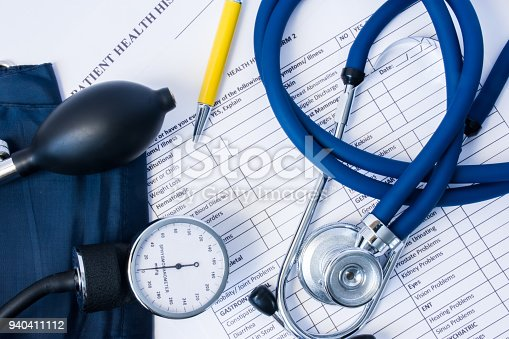 istock Diagnostic equipment - stethoscope, blood pressure gauge lying on patient health history and questionnaire of symptoms and the presence of previous disease. Scene with patient's physician consultation 940411112