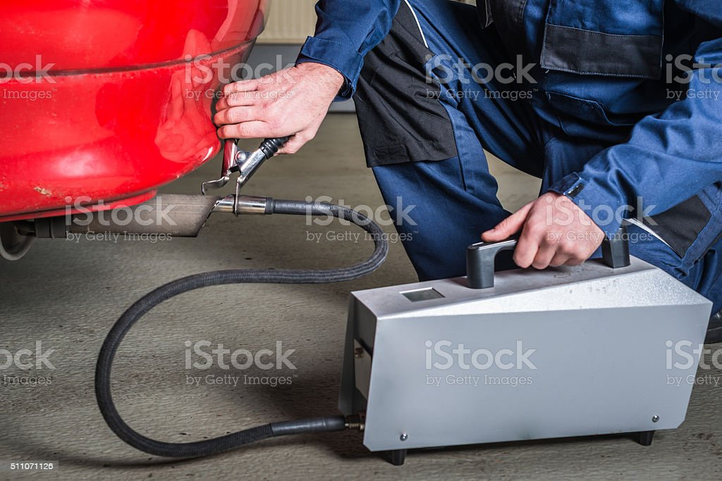 Diagnostic sensor is applied to the ehaust of red car stock photo