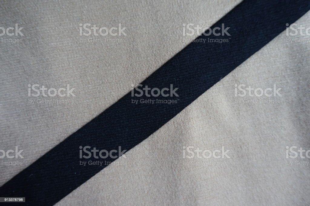 Diagonal black ribbon sewn to light grey fabric stock photo