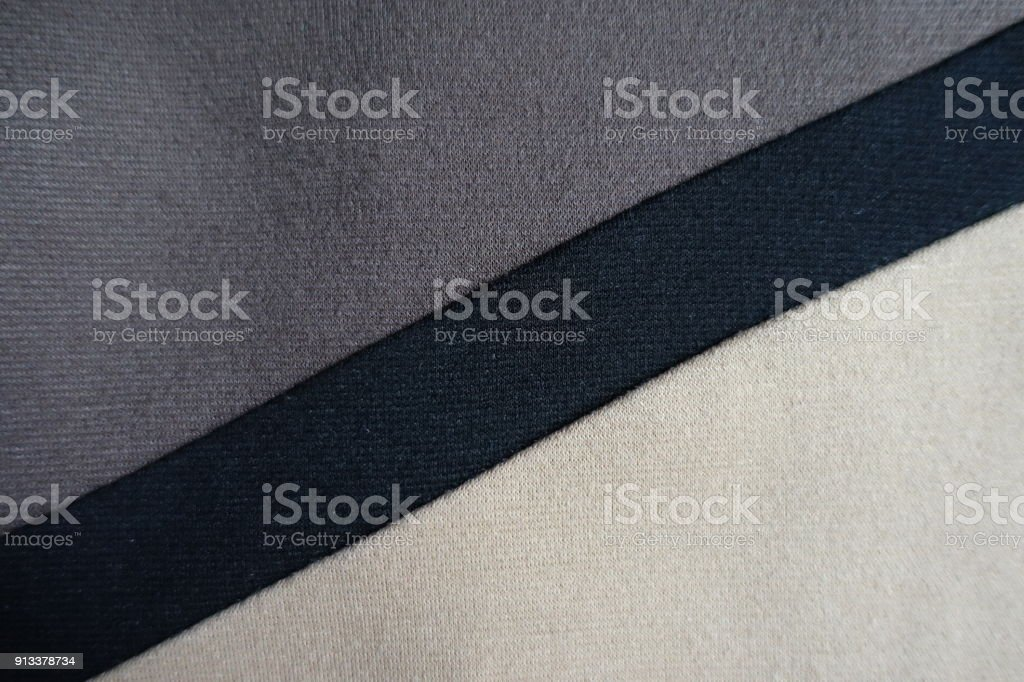 Diagonal black stripe sewn to grey and beige fabric stock photo