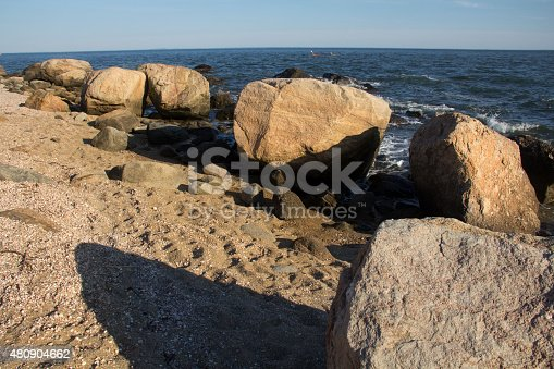 Diagonal line of granite, glacial boulders on gravel moraine at the beach in Hammonasset State Park, Madison, Connecticut.