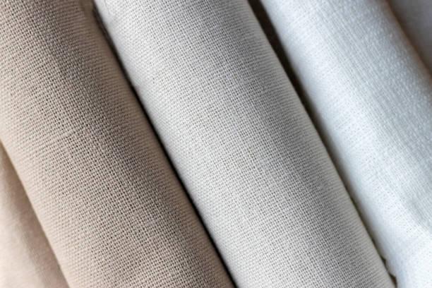 Fond textural diagonal de trois types de tissu naturel de lin, roulé. Mise au point sélective. Vue de plan rapproché - Photo