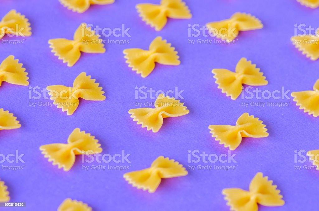 Diagonals of farfalle pasta on a violet background. - Foto stock royalty-free di Alimentazione sana