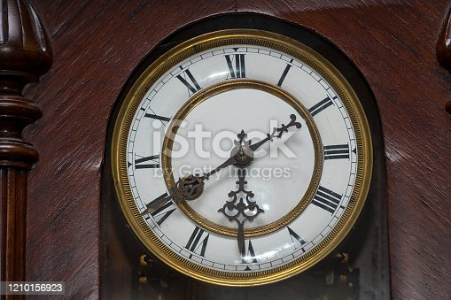 671883446 istock photo Dial of old wooden wall clock with Roman numerals 1210156923