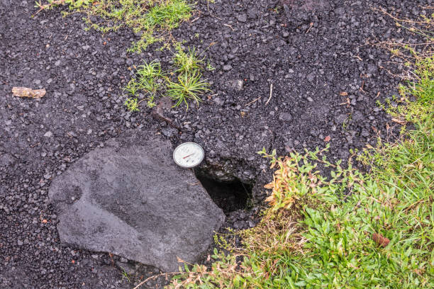 Dial placed in crack of road to measure temperature, Leilani Estate, Hawaii, USA. stock photo