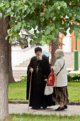 Sergiev Posad, Moscow District, Russia - July 4, 2009. Russian Orthodox priest talks talks with female parishioner in the Holy Trinity Lavra in Sergiev Posad (formerly known as Zagorsk), Moscow District, Russia. The Holy Trinity Lavra of St. Sergius is the most important Russian monastery and the spiritual centre of the Russian Orthodox Church. The monastery is located in Sergiev Posad, about 70 km to the north-east from Moscow. UNESCO declared it a World Heritage Site in 1993.