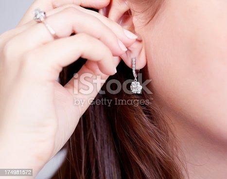 Woman putting on diamond earrings