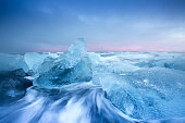 Stunning image of large pieces of 'diamond' like glacier ice washed up by the sea at sunset.