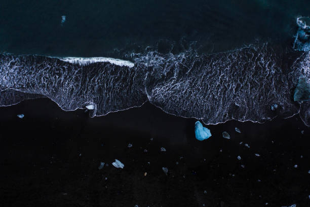 Diamond beach Iceland An aerial view of waves and melted icebergs approach black sandy beach of diamond beach in iceland black sand stock pictures, royalty-free photos & images