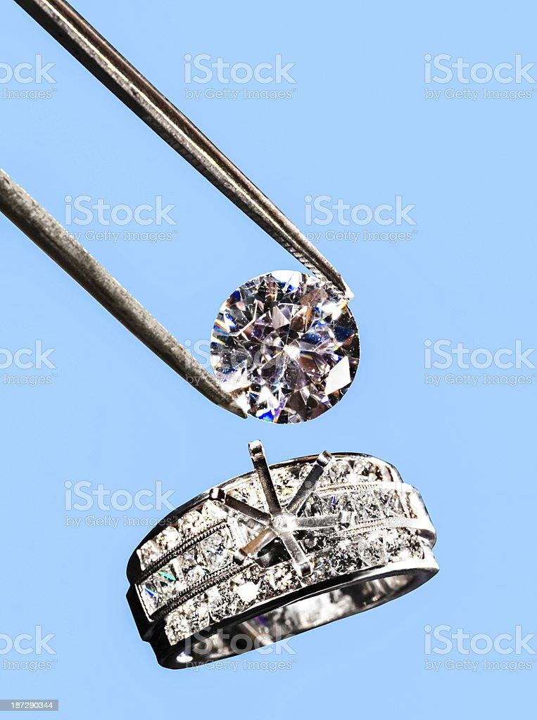 Diamond being set in wedding band stock photo