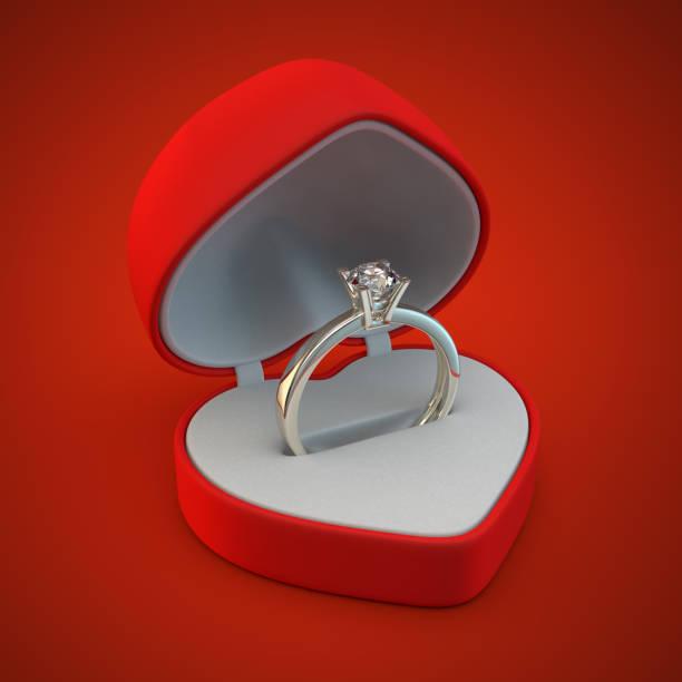 Anneau d'or de diamant dans la boîte de cadeau rouge de coeur - Photo