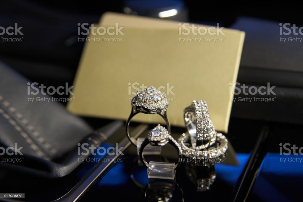 Diamond jewelry rings and earrings in the salon of a luxury car stock photo