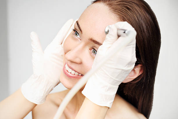 Diamond microdermabrasion Relaxed woman during a microdermabrasion treatment in beauty salon aha stock pictures, royalty-free photos & images