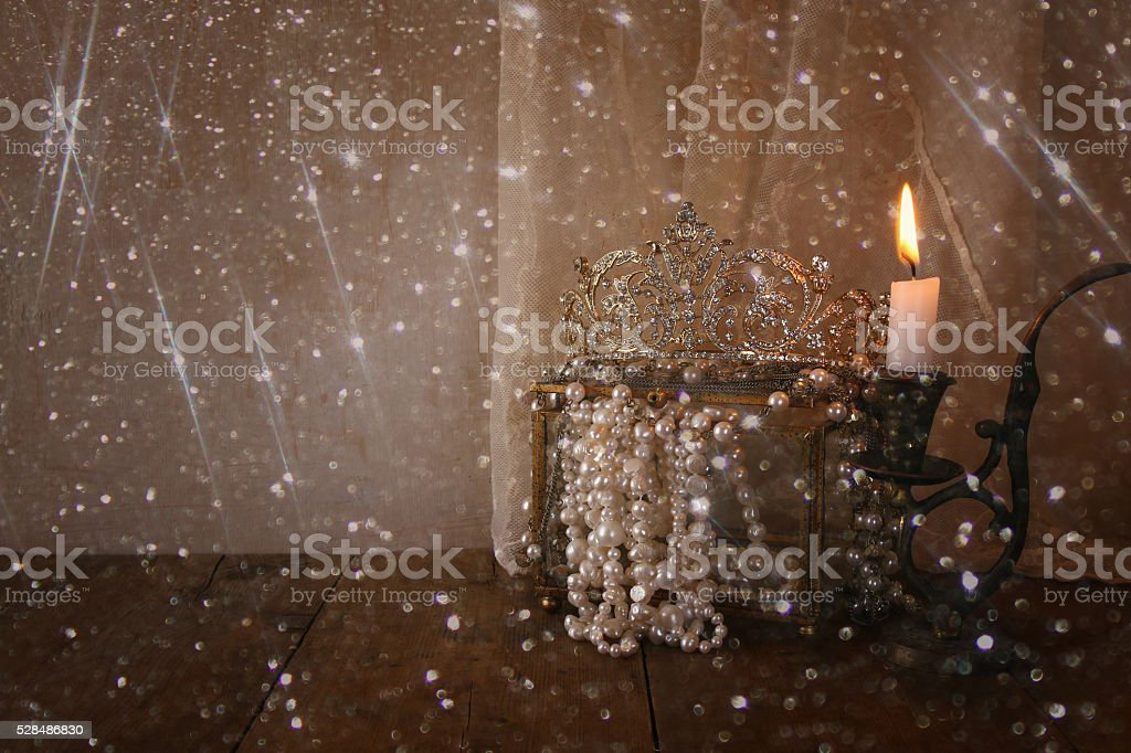 diamond queen crown, white pearls next to burning candle stock photo