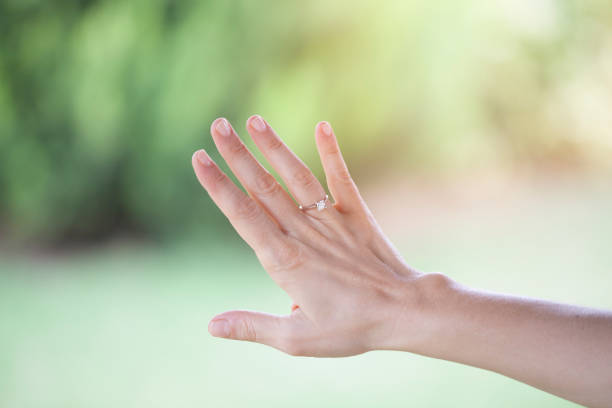 diamond ring in woman's hand - diamond ring hand stock pictures, royalty-free photos & images