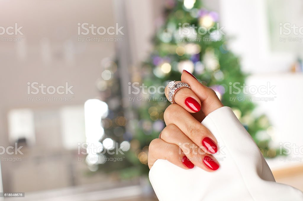 Diamond ring on a finger under the Christmas tree. stock photo
