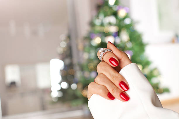 diamond ring on a finger under the christmas tree. - diamond ring hand stock photos and pictures