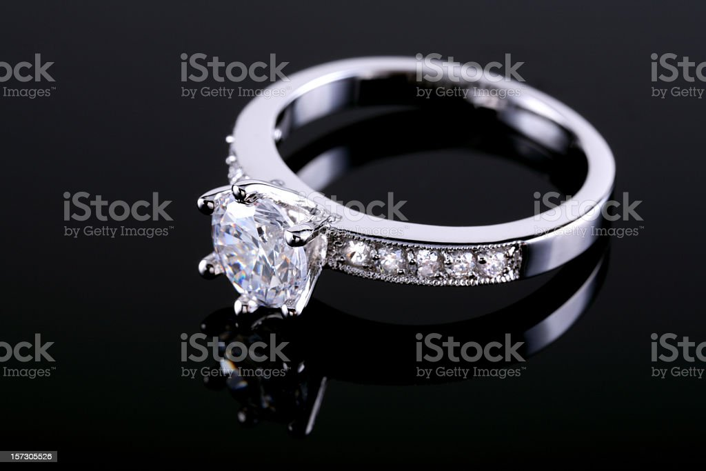 Diamond ring on a reflective surface stock photo
