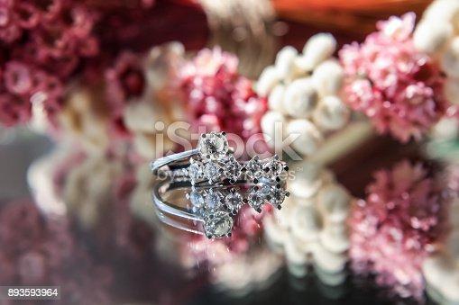 155315629istockphoto Diamond rings on flowered background 893593964