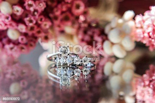 155315629istockphoto Diamond rings on flowered background 893593970