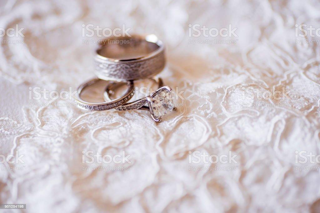 Diamond Wedding Rings On Top Of Wedding Dress Stock Photo