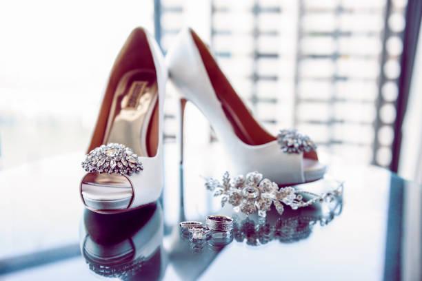 diamant-hochzeitsringe, schuhe und tiara - goldhochzeitsschuhe stock-fotos und bilder