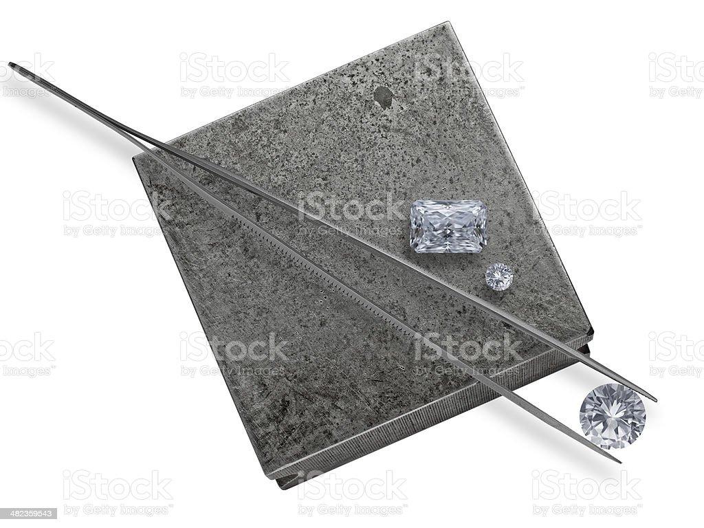 diamonds and tweezers on a jeweler anvil stock photo