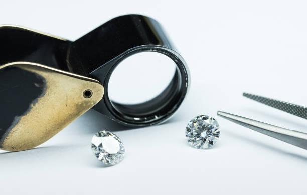 diamanten mit einer pinzette und loup - diamantschmuck stock-fotos und bilder