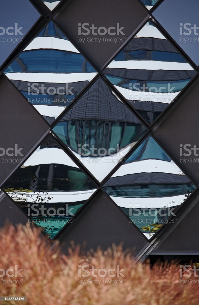 Diamondshaped Mirror Panels On An Exterior Wall Reflecting The Adjacent Buildings With Brown Vegetation In The Foreground Stock Photo Download Image Now Istock