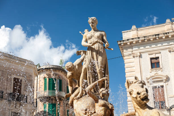Diana or Artemis Fountain, Syracuse, Sicily The Diana Fountain built in 1907 and surrounding buildings in the Archimedes square in the center of  Ortygia island in Syracuse, Sicily, Italy artemis stock pictures, royalty-free photos & images