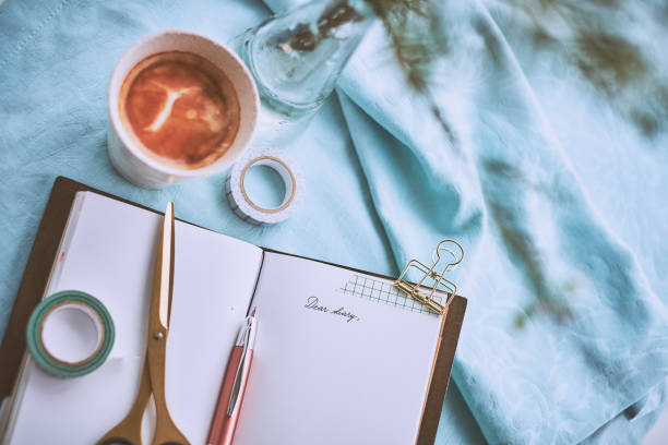 Diary and a cup of coffee on a turquoise napkin stock photo