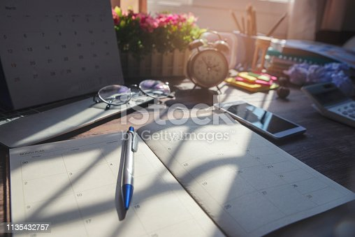 1073023470 istock photo Diary and smartphone for planning work schedules and appointments.Desktop laptop,calendar,clock,diary,books and glasses on wooden desk,Working space at home.Urban Lifestyle concept 1135432757