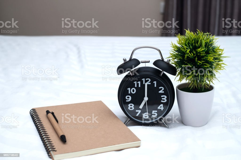 Diary or notebook and vintage alarm clock on bed in bedroom at home or hotel. zbiór zdjęć royalty-free