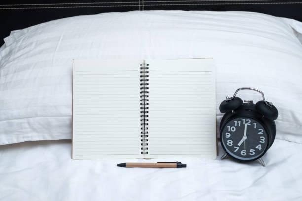 Yatak yatak odası evde veya otel günlüğü veya defter ve vintage çalar saat. stok fotoğrafı
