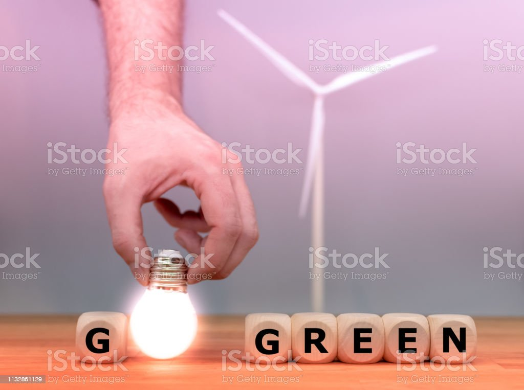 Dice and a light bulb form the words \'go green\' in front of a model...