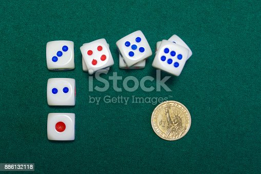 istock Dice and gold dollar on the green baize 886132118
