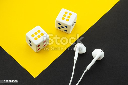 istock Dice and headphones on a black and yellow background 1036899088