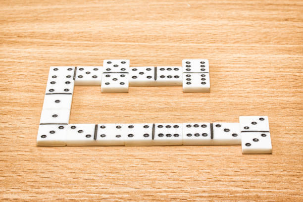 dice for playing dominoes on a wooden table stock photo