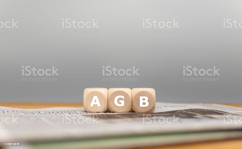 """Form des deutschen Ausdrucks AGB in Würfel schneiden (""""Allgemeine Geschäftsbedingungen"""" auf Englisch) vor einem grauen Hintergrund auf einer Zeitung. - Lizenzfrei Allgemein beschreibende Begriffe Stock-Foto"""