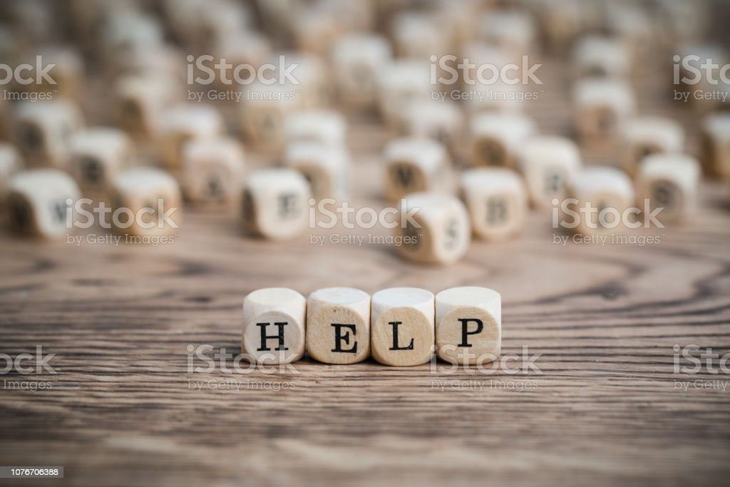 dice forming the word HELP wooden dice forming the word HELP on wooden background Advice Stock Photo