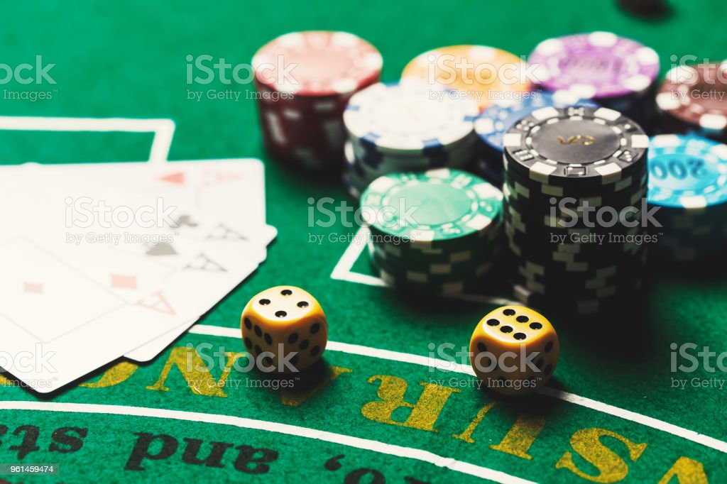 Dice on casino gamble table. Poker chips and banknotes on table in...