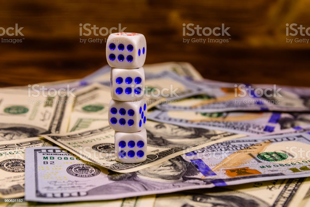 Dice on the one hundred dollar bills. Gamble concept stock photo