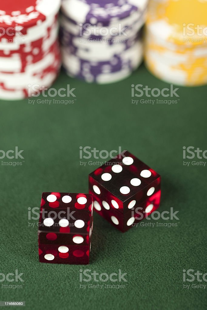 Dice showing a pair of sixes. Translucent red dice and gaming chips...