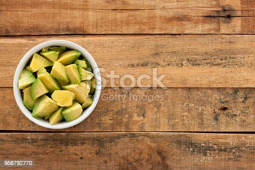 Top view of white bowl full of diced avocado over wooden table