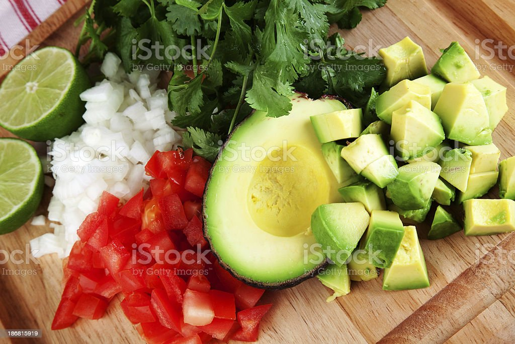 Diced avocado, tomato, and onion on chopping board stock photo