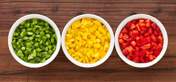 Diced pepper Top view of three bowls containing chopped green, yellow and red pepper yellow bell pepper stock pictures, royalty-free photos & images