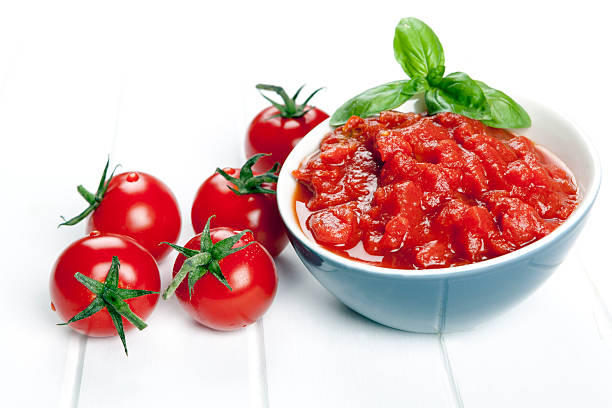 Diced Tomatoes Diced and whole tomatoes. garnished with basil.Diced and whole tomatoes, with olive oil behind.  Garnished with basil. crushed stock pictures, royalty-free photos & images