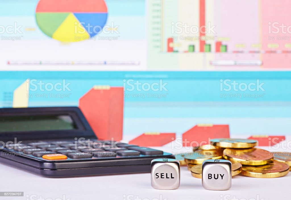 Dices cubes with the words BUY SELL, golden coins, calculator stock photo
