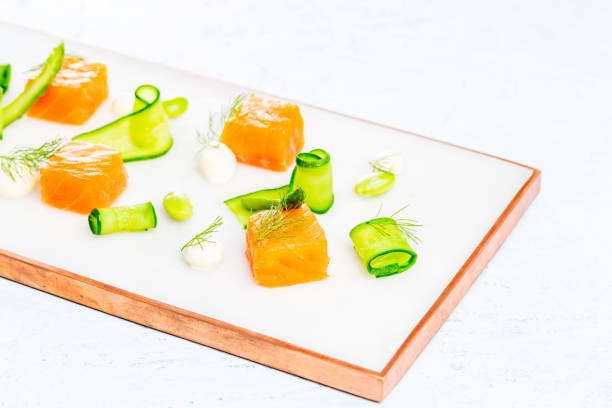 Dices of marinated salmon with asparagus, edamame beans, cream cheese and zucchini on a marble plate over a blue background. stock photo