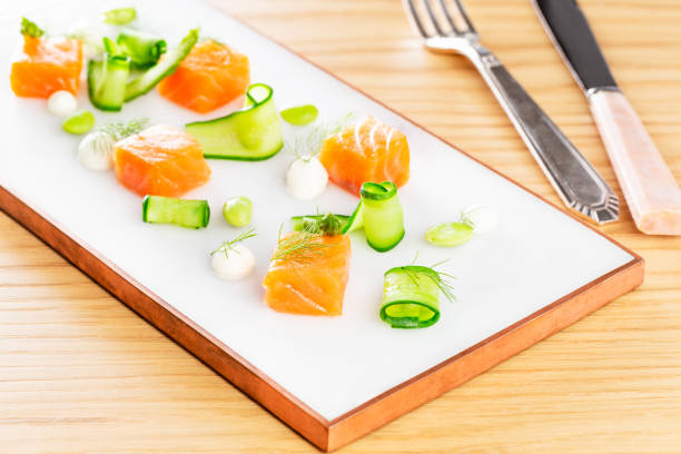 Dices of raw salmon with asparagus, edamame beans, cream cheese and zucchini on a marble plate aside a set of silver cutlery on a wood background. stock photo
